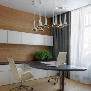 На фото: большое рабочее место в современном стиле с светлым паркетным полом, встроенным рабочим столом и бежевым полом с