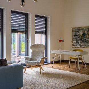 Неиссякаемый источник вдохновения для домашнего уюта: кабинет в скандинавском стиле с белыми стенами, паркетным полом среднего тона, отдельно стоящим рабочим столом и коричневым полом