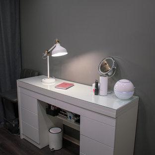 他の地域の小さいコンテンポラリースタイルのおしゃれな書斎 (グレーの壁、ラミネートの床、暖炉なし、造り付け机、茶色い床) の写真