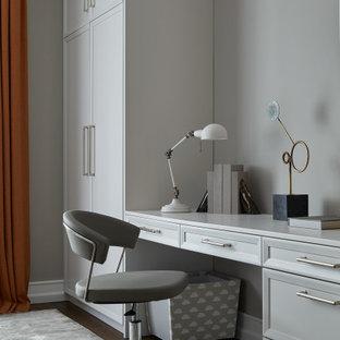 Стильный дизайн: кабинет в классическом стиле с серыми стенами, темным паркетным полом и встроенным рабочим столом - последний тренд