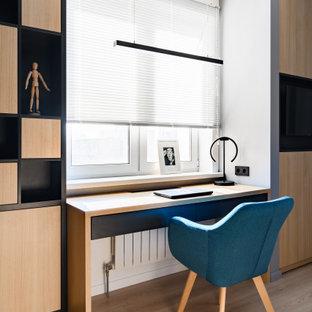 На фото: рабочее место среднего размера в современном стиле с белыми стенами, светлым паркетным полом, отдельно стоящим рабочим столом и бежевым полом