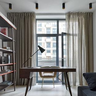 На фото: рабочее место среднего размера в современном стиле с серыми стенами, бетонным полом, отдельно стоящим рабочим столом и бежевым полом с