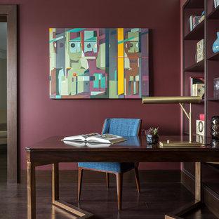 На фото: рабочее место среднего размера в стиле современная классика с красными стенами, темным паркетным полом, коричневым полом и отдельно стоящим рабочим столом без камина