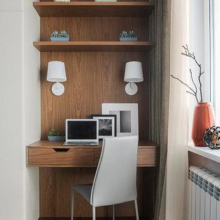 Inspiration för ett funkis hemmabibliotek, med mörkt trägolv, ett inbyggt skrivbord, brunt golv och bruna väggar