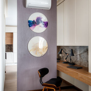 Неиссякаемый источник вдохновения для домашнего уюта: рабочее место в современном стиле с фиолетовыми стенами, встроенным рабочим столом, паркетным полом среднего тона и коричневым полом