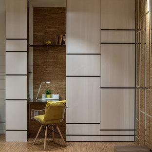 Idéer för mellanstora funkis hemmabibliotek, med vita väggar, korkgolv och ett inbyggt skrivbord