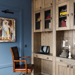 Пример оригинального дизайна: рабочее место в классическом стиле с синими стенами, паркетным полом среднего тона, встроенным рабочим столом и коричневым полом