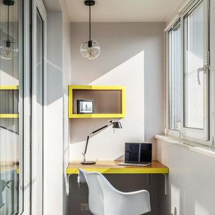 Пример оригинального дизайна: рабочее место в современном стиле с белыми стенами и серым полом без камина