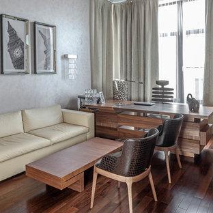 Идея дизайна: рабочее место среднего размера в современном стиле с серыми стенами, темным паркетным полом, отдельно стоящим рабочим столом и коричневым полом