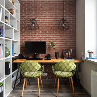 Пример оригинального дизайна: маленькое рабочее место в современном стиле с полом из ламината, отдельно стоящим рабочим столом и красными стенами без камина