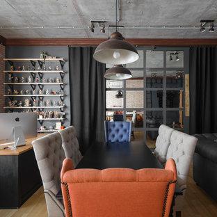 他の地域の広いインダストリアルスタイルのおしゃれな書斎 (黒い壁、ラミネートの床、自立型机、茶色い床) の写真