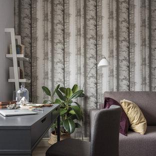 На фото: рабочее место среднего размера в стиле современная классика с серыми стенами, светлым паркетным полом, отдельно стоящим рабочим столом и серым полом без камина