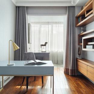 На фото: рабочее место среднего размера в современном стиле с серыми стенами, паркетным полом среднего тона, отдельно стоящим рабочим столом и коричневым полом