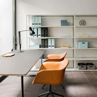На фото: рабочее место среднего размера в стиле модернизм с белыми стенами, отдельно стоящим рабочим столом, полом из керамогранита и серым полом с