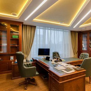 На фото: рабочее место в классическом стиле с коричневыми стенами, паркетным полом среднего тона, отдельно стоящим рабочим столом и коричневым полом с