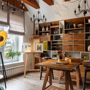 Пример оригинального дизайна интерьера: домашняя мастерская в современном стиле с белыми стенами, паркетным полом среднего тона, горизонтальным камином, отдельно стоящим рабочим столом и коричневым полом