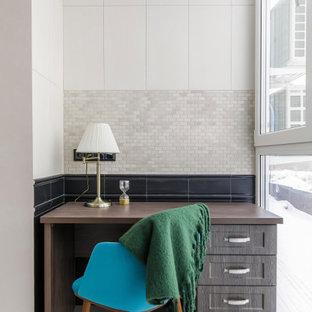 На фото: рабочее место среднего размера в стиле современная классика с белыми стенами, полом из керамогранита, отдельно стоящим рабочим столом и серым полом