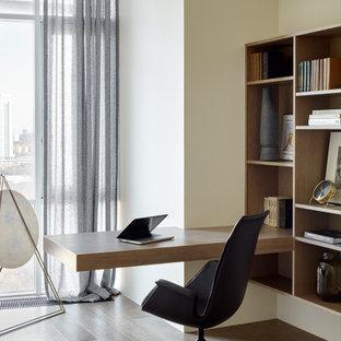 Неиссякаемый источник вдохновения для домашнего уюта: рабочее место среднего размера в современном стиле с бежевыми стенами, паркетным полом среднего тона, встроенным рабочим столом и коричневым полом
