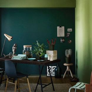Пример оригинального дизайна: рабочее место в современном стиле с зелеными стенами, паркетным полом среднего тона, отдельно стоящим рабочим столом и коричневым полом