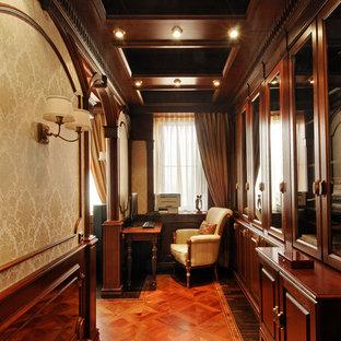 На фото: кабинеты в классическом стиле с рабочим местом, коричневыми стенами, паркетным полом среднего тона и отдельно стоящим рабочим столом