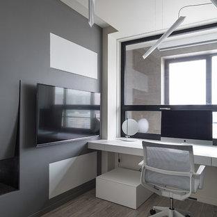 Ejemplo de despacho escandinavo con paredes grises, chimenea de doble cara, escritorio empotrado y suelo de madera en tonos medios