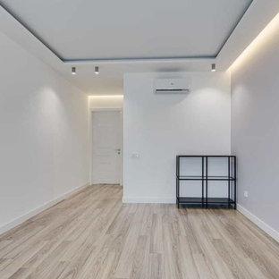 Modelo de despacho grande con paredes blancas, suelo de madera en tonos medios y suelo multicolor