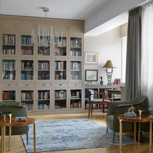 Источник вдохновения для домашнего уюта: домашняя библиотека в современном стиле с бежевыми стенами, паркетным полом среднего тона, отдельно стоящим рабочим столом и коричневым полом