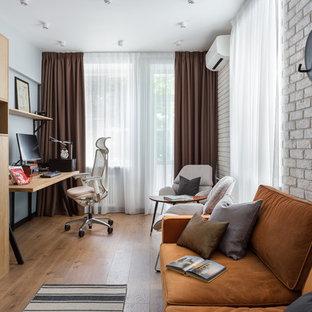 Пример оригинального дизайна: маленький кабинет в скандинавском стиле с белыми стенами, полом из ламината и коричневым полом без камина
