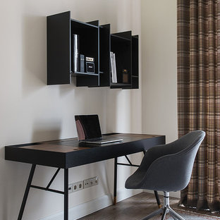 На фото: маленькое рабочее место в современном стиле с бежевыми стенами, отдельно стоящим рабочим столом, коричневым полом и темным паркетным полом с