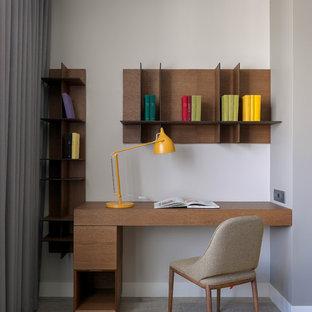 Неиссякаемый источник вдохновения для домашнего уюта: маленькое рабочее место в современном стиле с серыми стенами, паркетным полом среднего тона, встроенным рабочим столом и серым полом