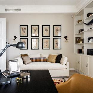 Пример оригинального дизайна: рабочее место в стиле современная классика с бежевыми стенами, отдельно стоящим рабочим столом и светлым паркетным полом