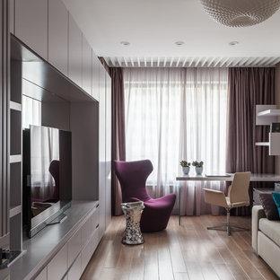 Пример оригинального дизайна: рабочее место в современном стиле с бежевыми стенами, паркетным полом среднего тона, отдельно стоящим рабочим столом и коричневым полом