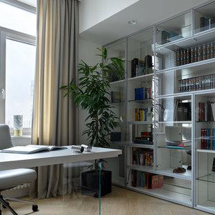 Неиссякаемый источник вдохновения для домашнего уюта: кабинет в современном стиле с серыми стенами, светлым паркетным полом, встроенным рабочим столом, бежевым полом и библиотекой