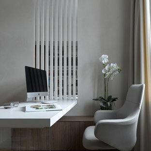 На фото: рабочее место в современном стиле с серыми стенами, светлым паркетным полом, встроенным рабочим столом и бежевым полом