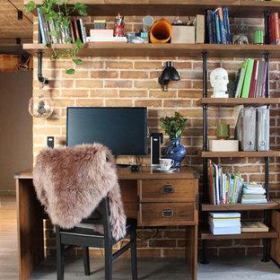 モスクワの中くらいのインダストリアルスタイルのおしゃれなホームオフィス・書斎 (ライブラリー、ラミネートの床、暖炉なし、グレーの床、オレンジの壁、自立型机) の写真