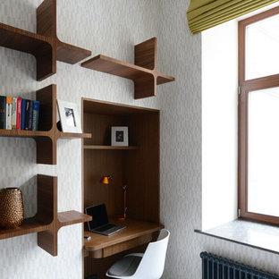 Ejemplo de despacho actual, pequeño, con paredes blancas, suelo de madera pintada y escritorio empotrado