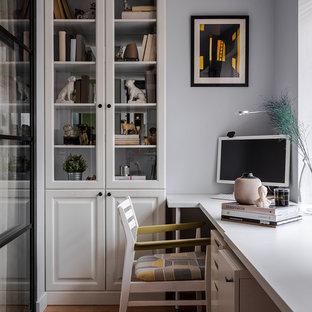 Foto på ett funkis arbetsrum, med grå väggar, mellanmörkt trägolv, ett fristående skrivbord och brunt golv