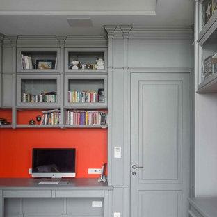 Идея дизайна: рабочее место среднего размера в стиле неоклассика (современная классика) с серыми стенами, светлым паркетным полом, встроенным рабочим столом, бежевым полом, стандартным камином и фасадом камина из дерева