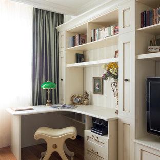 Стильный дизайн: кабинет среднего размера в классическом стиле с бежевыми стенами, паркетным полом среднего тона, встроенным рабочим столом и библиотекой - последний тренд