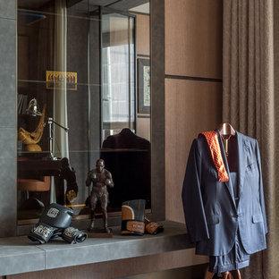 Immagine di un ufficio minimal di medie dimensioni con pareti marroni, parquet scuro, scrivania autoportante, pavimento marrone, camino sospeso e cornice del camino in metallo
