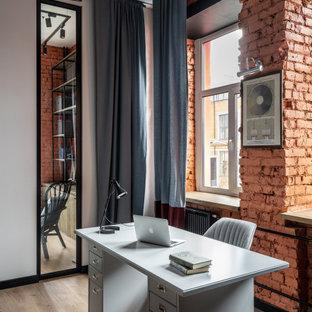 Стильный дизайн: кабинет в стиле лофт с серыми стенами, паркетным полом среднего тона, отдельно стоящим рабочим столом, коричневым полом и кирпичными стенами - последний тренд