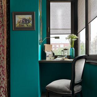 Kleines Eklektisches Arbeitszimmer mit Arbeitsplatz, blauer Wandfarbe, dunklem Holzboden und Einbau-Schreibtisch in Moskau