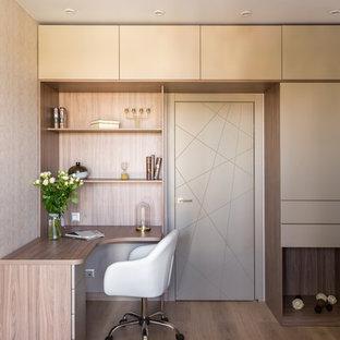 Пример оригинального дизайна: кабинет в современном стиле с бежевыми стенами, паркетным полом среднего тона, встроенным рабочим столом и коричневым полом