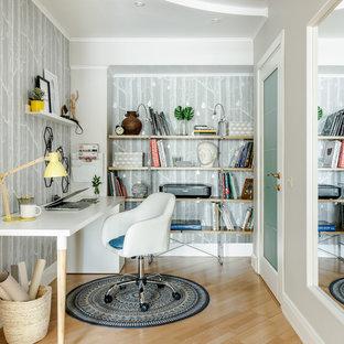 На фото: рабочее место в скандинавском стиле с серыми стенами, светлым паркетным полом, отдельно стоящим рабочим столом и бежевым полом с