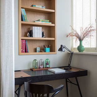 Идея дизайна: маленькое рабочее место в современном стиле с серыми стенами, паркетным полом среднего тона и отдельно стоящим рабочим столом без камина
