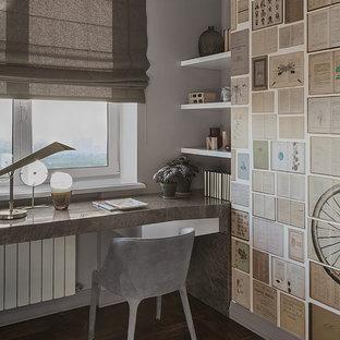 На фото: рабочее место в современном стиле с серыми стенами, темным паркетным полом, встроенным рабочим столом и коричневым полом с