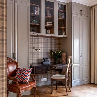 Imagen de despacho tradicional, de tamaño medio, con paredes grises, suelo de madera en tonos medios, escritorio independiente y suelo amarillo