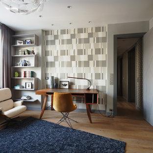 Пример оригинального дизайна интерьера: рабочее место в современном стиле с паркетным полом среднего тона, отдельно стоящим рабочим столом и разноцветными стенами без камина
