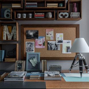 Пример оригинального дизайна: рабочее место в стиле неоклассика (современная классика) с серыми стенами и отдельно стоящим рабочим столом