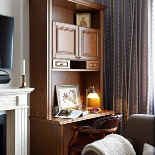 Неиссякаемый источник вдохновения для домашнего уюта: рабочее место в классическом стиле с бежевыми стенами, темным паркетным полом, стандартным камином, отдельно стоящим рабочим столом и коричневым полом